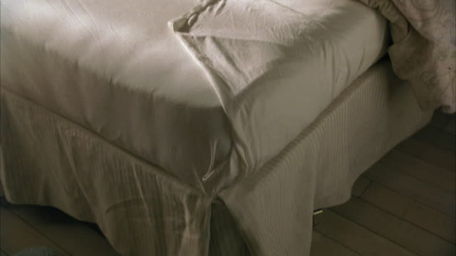 HIGH ANGLE DOWN OF UNMADE BED WITH WHITE SHEETS AND COMFORTER.