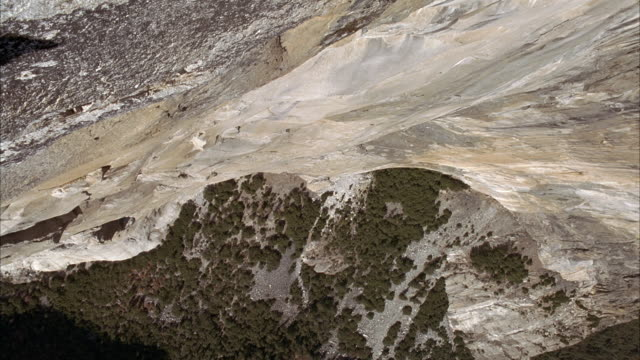 high angle down, from peak of el capitan to valley of green trees below. yosemite national park. - el capitan yosemite national park stock videos and b-roll footage