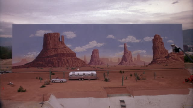est. medium angle of painted backdrop of monument valley.  see silver trailer home, mercedes-benz 300 sl parked in front. see cactus surrounding trailer. could be desert setting on movie studio lot. - trailer home stock videos & royalty-free footage