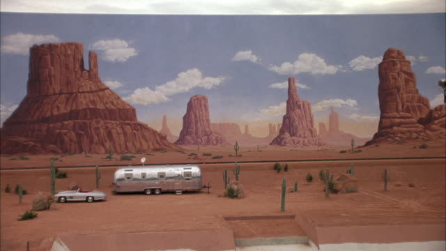 medium angle of painted backdrop of monument valley.  zooms in to see silver trailer home, mercedes-benz 300 sl parked in front. - trailer home stock videos & royalty-free footage