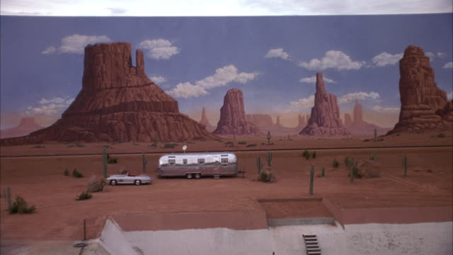 medium angle of painted backdrop of monument valley.  zooms in to see silver trailer home, mercedes-benz 300 sl parked in front. see cactus surrounding trailer. could be desert setting on movie studio lot. - trailer home stock videos & royalty-free footage