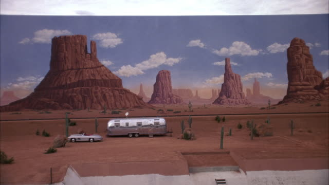 medium angle of painted backdrop of monument valley.  zooms in to see silver trailer home, mercedes-benz 300 sl parked in front. see parked trailer move up and down in place. see cactus surrounding trailer. could be desert setting on movie studio lot. - trailer home stock videos & royalty-free footage