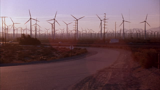MEDIUM ANGLE GROUPS OF WIND TURBINES, ELECTRICITY GENERATORS, SOME REVOLVING. SEE HIGHWAY IN FRONT OF TURBINES, TRAFFIC MOVING IN BOTH LANES. SEE BLUE RENAULT LE CAR APPROACH ON ROAD. ENERGY, POWER PLANTS.