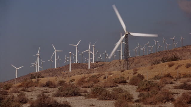 medium angle group of wind turbines, electricity generators. mountains in background. see blue renault le car drive left to right on road in foreground. energy, power plants. - generator stock videos & royalty-free footage
