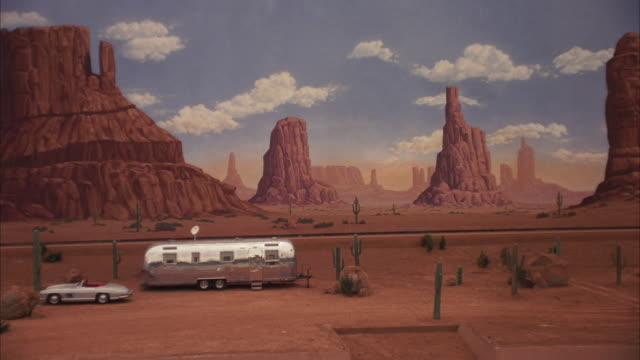 pull back of painted backdrop of monument valley. zooms in to see silver trailer home, mercedes-benz 300 sl parked in front. then pulls back out. see cactus surrounding trailer. could be desert setting on movie studio lot. - trailer home stock videos & royalty-free footage