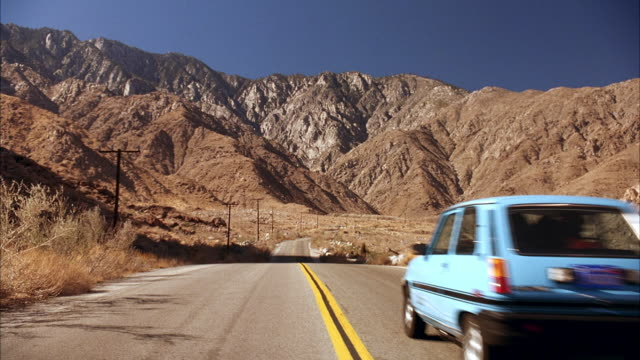 MEDIUM ANGLE SIGN, 'WELCOME TO PALM SPRINGS, POPULATION 43,000' BESIDE HIGHWAY. SEE MOUNTAINS IN BACKGROUND, ROCKS PILED NEAR SIGN. PAN LEFT TO RIGHT, SEE BLUE RENAULT LE CAR DRIVE AWAY FROM POV ON HIGHWAY.