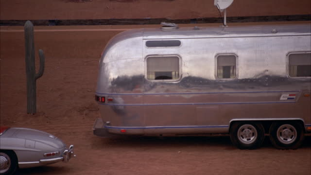 medium angle of silver trailer home, mercedes-benz 300 sl parked in front. pulls back to see painted backdrop of monument valley. see cactus surrounding trailer. could be desert setting on movie studio lot. - trailer home stock videos & royalty-free footage