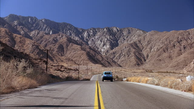 MEDIUM ANGLE ROAD, MOUNTAINS IN BACKGROUND, TUMBLEWEEDS OR BRUSH ALONG ROAD. SEE BLUE RENAULT LE CAR ENTER FRAME, DRIVING AWAY FROM POV ON HIGHWAY.