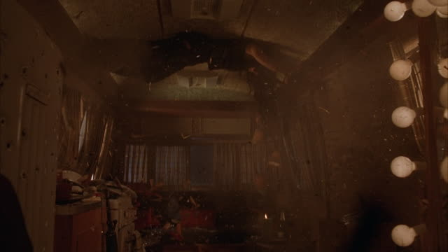 medium angle of stunt inside trailer home. moving pov to see gunfire shoot through kitchen of trailer home. see woman dressed in black hang horizontally along ceiling to avoid gun shots. - see other clips from this shoot 2316 stock-videos und b-roll-filmmaterial