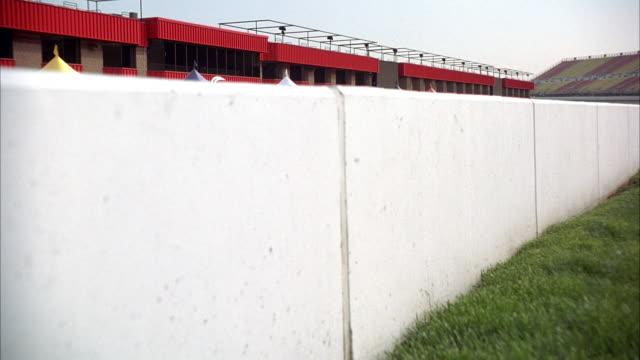 MEDIUM ANGLE SHORT WHITE CONCRETE WALL ON LEFT AND GREEN GRASS NEXT TO IT. PAN UP TO SEE RACETRACK ON OVERCAST DAY.