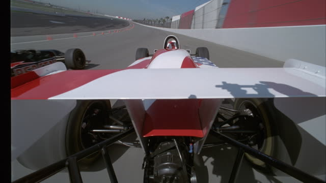 PROCESS PLATE OF BACK OF WHITE FORMULA ONE RACE CAR WITH RED STRIPES PASSING BLACK FORMULA ONE RACE CAR WITH RED STAR ON RACE TRACK.