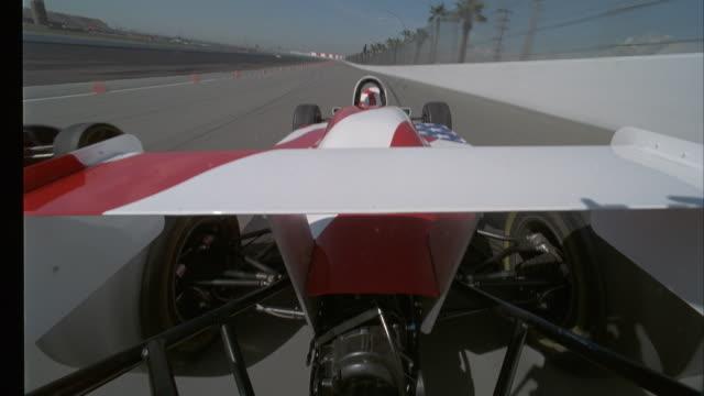 vídeos y material grabado en eventos de stock de process plate of back of white formula one race car with red stripes passing black formula one race car with red star on race track. - formula 1