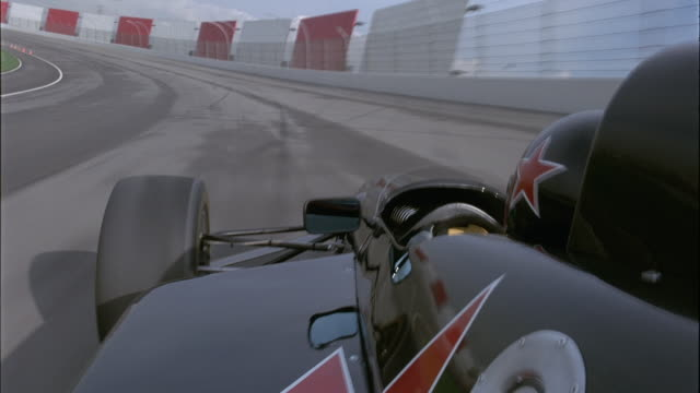 PROCESS PLATE ON RIGHT SIDE OF BLACK FORMULA ONE CAR WITH RED STAR ON SIDE SPEEDING DOWN RACETRACK. SEE CHAIN LINK FENCE ON A SHORT CONCRETE WALL OUTLINING RIGHT SIDE OF TRACK.