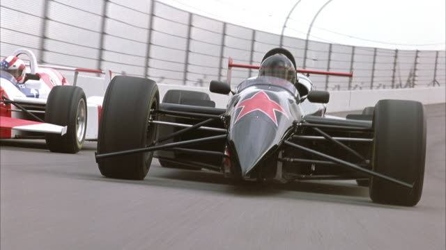 PROCESS PLATE OF BLACK FORMULA ONE RACE CAR WITH RED STAR ON FRONT AND RED AND WHITE STRIPED FORMULA ONE RACE CAR BEGIN RACING ON RACE TRACK TOWARDS POV.