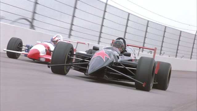 HAND HELD OF BLACK FORMULA ONE RACE CAR WITH RED STAR ON FRONT SPEEDING ON RACE TRACK TOWARDS POV. SEE POV PAN DOWN TO CONCRETE OF RACE TRACK AND PAN BACK UP.