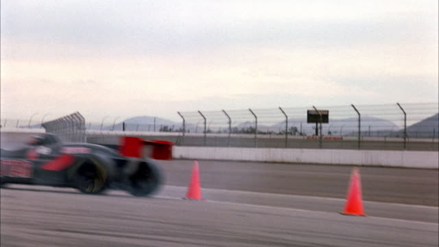 "HAND HELD OF SIDE OF BLACK FORMULA ONE RACE CAR WITH RED STAR AND TEXT ON SIDE READING ""REDSTAR"" SPEEDING TO LEFT WITH SMOKE RISING FROM TIRES. TRACK RACE CAR AS SPEEDS LEFT AND AWAY FROM POV ON RACE TRACK"