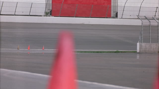 HAND HELD OF BEND IN RACE TRACK. SEE CHAIN LINK FENCE ON RIGHT OF POV. SEE RACE TRACK POSITIONED PERPENDICULAR TO POV.