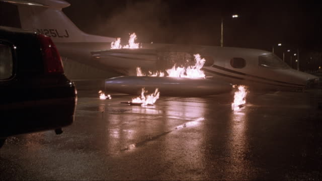 medium angle of jet situated perpendicular to street on fire in bg and black lincoln limousine parked in left fg. - limousine luxuswagen stock-videos und b-roll-filmmaterial