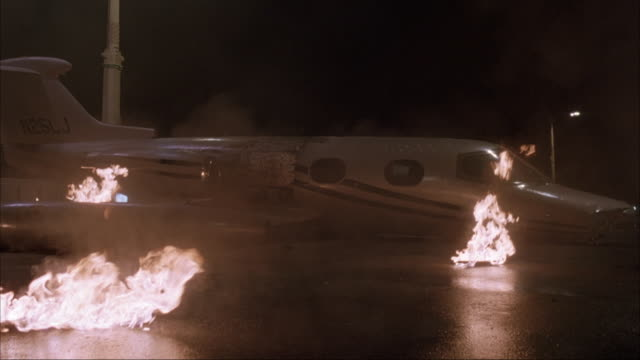 wide angle of jet in bg with fire on ground and in jet engine.  jet situated perpendicular to street as if it just crashed. 40 fps slow motion. action. - airplane crash stock videos and b-roll footage