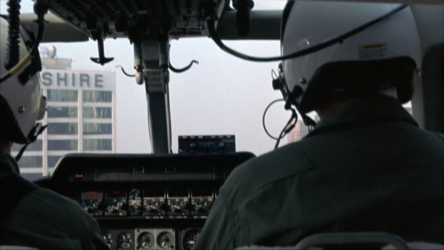 "medium angle. inside helicopter cockpit. pilot and co-pilot in front of helicopter. flying through downtown los angeles. see ""one wilshire"" building as helicopter passes. - helicopter stock videos & royalty-free footage"
