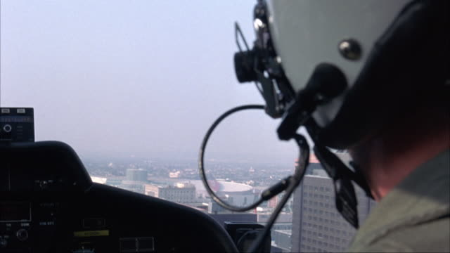 MEDIUM ANGLE. LOOKING OVER SHOULDER OF CO-PILOT IN HELICOPTER. FLIES UP TO ROOF OF HIGH RISE BUILDING WITH S.W.A.T TEAM ESCORTING PRISONER ON TOP. HELICOPTER THEN FLIES AWAY FROM ROOFTOP.