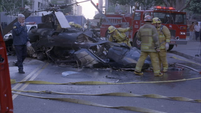 vídeos de stock e filmes b-roll de medium angle of firemen cleaning up mess from helicopter crash. see burnt helicopter on street. fire truck parked on street. - impacto