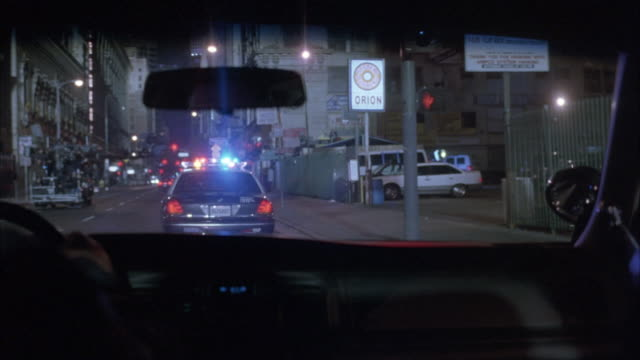 MEDIUM ANGLE FROM POV OF BACKSEAT OF POLICE CAR FOLLOWING ANOTHER SQUAD CAR DRIVING DOWN CITY STREET.  POLICE LIGHTS ARE FLASHING.  CAR CRASHES INTO CIVILIAN CAR PULLING OUT FROM CURB.