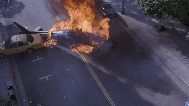 vídeos de stock e filmes b-roll de high angle down on city street. see lapd helicopter crashing down to street and yellow taxi swerves sharply to avoid collision with helicopter. - impacto