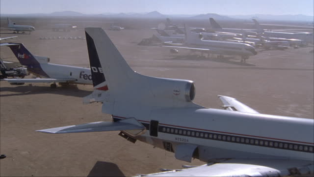 aerial over large commercial airliner in desert airport. zooms in and passes by swat member on top of plane. pans up and away from ground - deserto mojave video stock e b–roll
