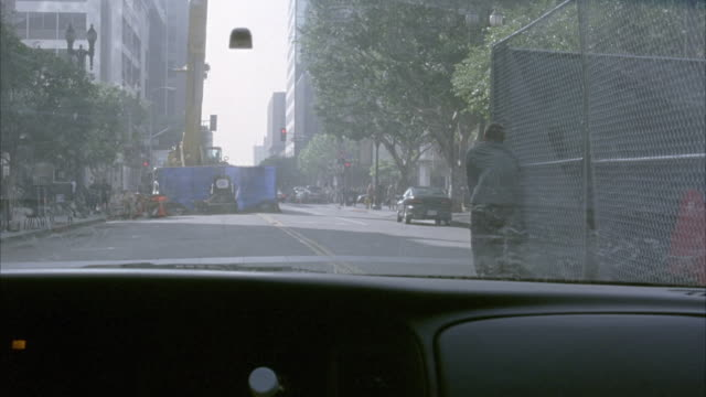 medium angle. pov from passenger side. driving down city street. see lapd helicopter crash down in front of car and explode. car swerves sharply to left to avoid collision with explosion. car knocks over mailbox. driver ducks down. explosions. - ヘリコプター事故点の映像素材/bロール
