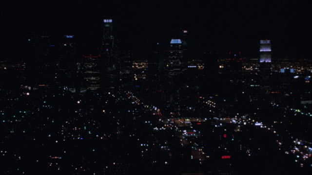 aerial. moving past high rise buildings in downtown los angeles at night. shot moves away from buildings and pulls back shot. zooms back in and gets closer to buildings. circling around us bank tower, citigroup building, and other high rise buildings. - us bank tower stock videos & royalty-free footage