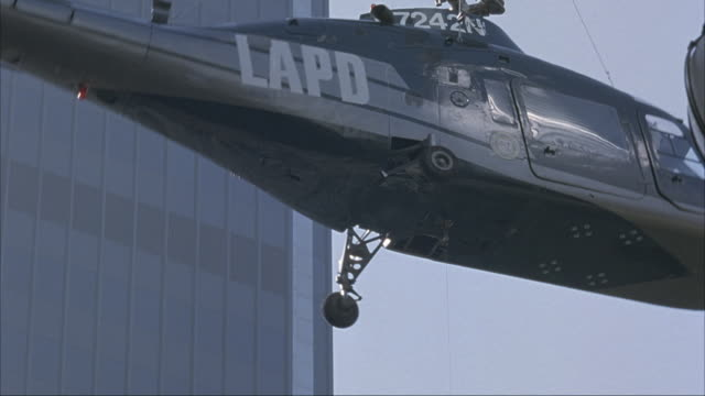up angle at lapd helicopter spinning in circles. see office buildings in bg.  helicopter eventually crashes straight down into city street, exploding. yellow taxi swerves sharply to avoid collision with explosion. explosions. - ヘリコプター事故点の映像素材/bロール