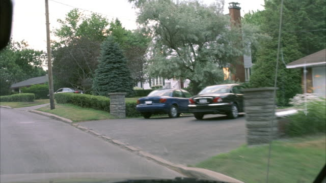 WIDE ANGLE. INSIDE CAR POV DRIVING DOWN RESIDENTIAL STREET. CAR DRIVES DOWN STREET THEN SLOWS TO A STOP IN FRONT OF WHITE TWO-STORY HOUSE WITH BLACK AUDI SEDAN PARKED IN DRIVEWAY. TWO SILHOUETTES IN SECOND STORY WINDOW.