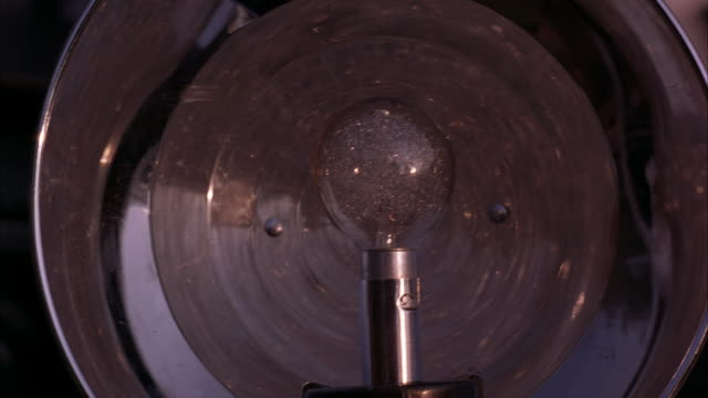CLOSE ANGLE OF LARGE FLASH BULB OF VINTAGE CAMERA. FLASH POPS. PHOTOGRAPHER LOWERS CAMERA AT END. INSERT.