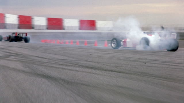 HAND HELD OF RED AND WHITE STRIPED FORMULA ONE RACE CAR SPINNING AROUND ON RACE TRACK WITH SMOKE COMING OUT FROM TIRES. SEE PALM TRESS ON OUTSIDE OF CHAIN LINK FENCE LINING RACE TRACK ON LEFT.