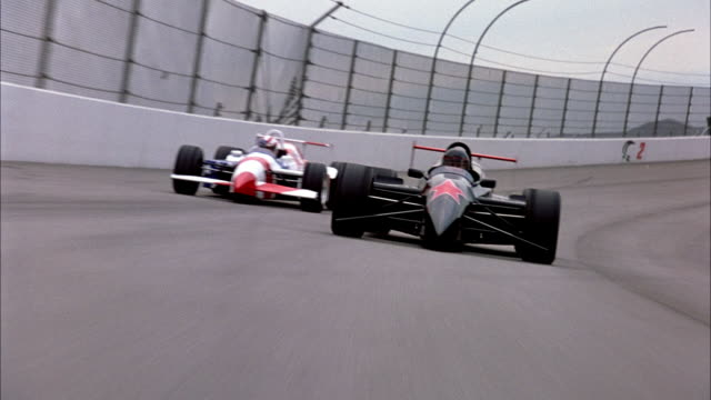 hand held of black formula one race car with red star on front racing next to formula one race car painted like american flag towards pov. - formula one racing stock videos & royalty-free footage