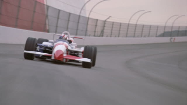 PROCESS PLATE OF AMERICAN FLAG PAINTED FORMULA ONE RACE CAR DRIVING TOWARD POV ON RACE TRACK. SEE SHORT WHITE CONCRETE WALL ON LEFT OF TRACK. SEE DARK CLOUDS IN SKY. SHOT IN 16 FPS TIME LAPSE OR FAST MOTION.