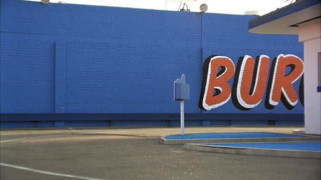 "MEDIUM ANGLE OF BACK ALLEY OF DRIVE-THRU OR FAST FOOD RESTAURANT. GRAFFITI READING ""BUR"" AS IN BURGERS IN RED, WHITE AND BLACK LETTERS ON BLUE WALL IN BACKGROUND."