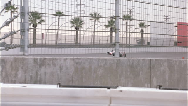 medium angle of race track running perpendicular to pov. see palm trees in background and chain link fence in foreground obstructing view of race track. - fence stock videos & royalty-free footage