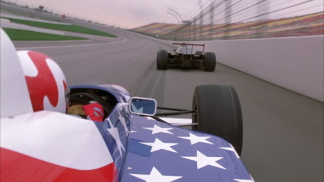 PROCESS PLATE OF FROM RIGHT SIDE BEHIND DRIVER OF FORMULA ONE RACE CAR PAINTED WITH AMERICAN FLAG PATTERN. SEE RACE CAR FOLLOWING BLACK FORMULA ONE RACE CAR WITH RED SPOILER AND ACCENTS