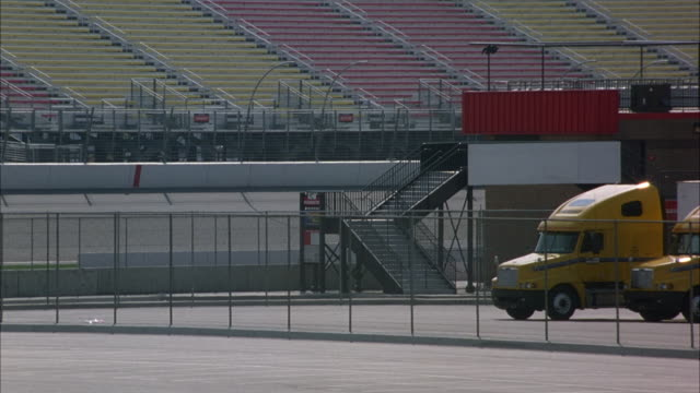 medium angle of race track from asphalt parking lot at center of track. see two yellow semi trucks parked at right behind chain link fence. - 駐車場点の映像素材/bロール