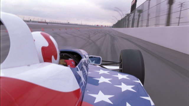 PROCESS PLATE OF LEFT SIDE LOOKING FORWARD OF FORMULA ONE CAR PAINTED LIKE AN AMERICAN FLAG RACING BLACK FORMULA ONE CAR ON RACE TRACK.