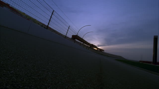 medium skewed angle from middle of asphalt of racing track. see metal fencing and white barrier at left and grassy center of track at right. - tarmac stock videos & royalty-free footage
