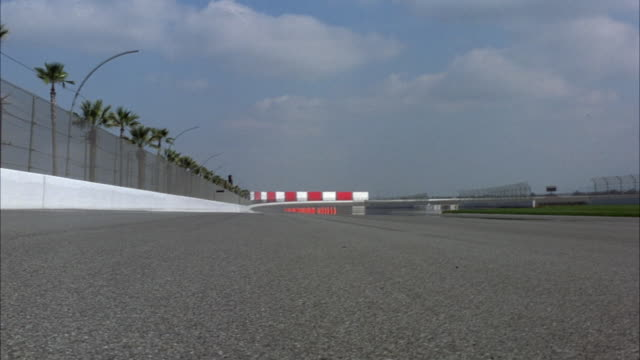 medium angle from asphalt of straightaway of formula one race track. see palm tress behind chain link fence at left and green grass at center of track at right. see orange cones lining bend of track. see some cumulus clouds in blue sky. - fence stock videos & royalty-free footage