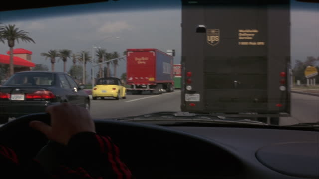 process plate from passenger seat of interior of car behind ups truck. see hands holding steering wheel at left. see pov switch into left lane. - tow truck driver stock videos and b-roll footage