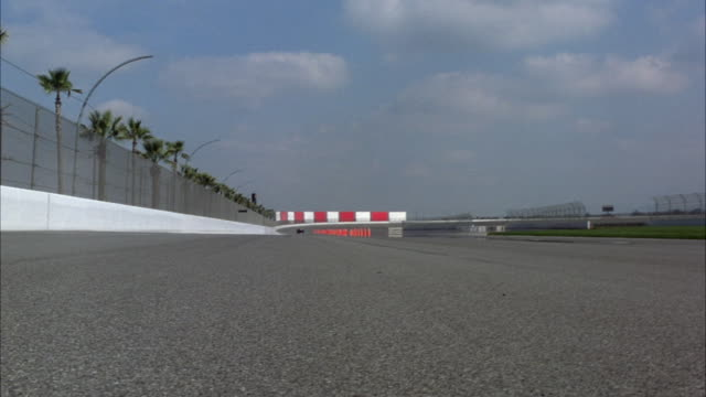 medium angle from asphalt of straightaway of formula one race track. see palm tress behind chain link fence at left and green grass at center of track at right. - fence stock videos & royalty-free footage