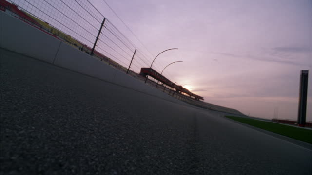 medium skewed angle from middle of asphalt of racing track. see metal fencing and white barrier at left and grassy center of track at right. - asfalto video stock e b–roll