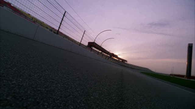 vídeos y material grabado en eventos de stock de medium skewed angle from middle of asphalt of racing track. see metal fencing and white barrier at left and grassy center of track at right. see two formula one race cars round bend and approach pov. - formula 1