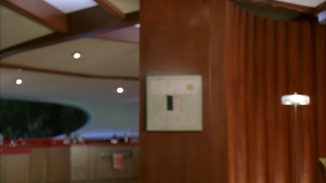 medium angle of rooms in modern house. wood paneled walls, tan carpet. red countertop, kitchen in background. interior modeled on chemosphere house by architect john lautner. upper class. matching clips 2219-057, 2219-058, 2320-046, 2320-047. - 2000 2010 stil bildbanksvideor och videomaterial från bakom kulisserna
