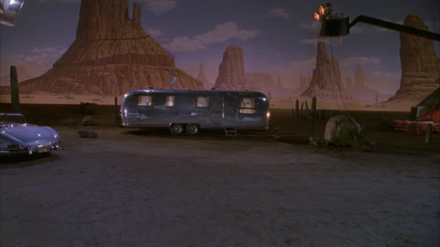 vídeos de stock e filmes b-roll de medium angle of silver or chrome air stream trailer parked in front of monument valley backdrop.  see cactus and boulders in sand around trailer. - penedo